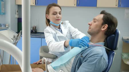 лечение зубов : Dental doctor preparing patient for treatment Стоковые видеозаписи