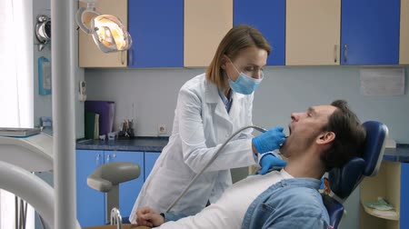 treating : Male patient receiving tooth decay treatment