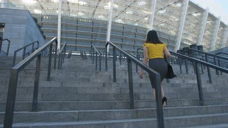 vysoký : Business woman walking up stairs to office center