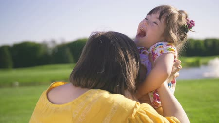 łaskotki : Mom and down syndrome daughter enjoying outdoors Wideo