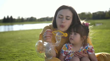 needs : Mom and special daughter blowing bubbles in park