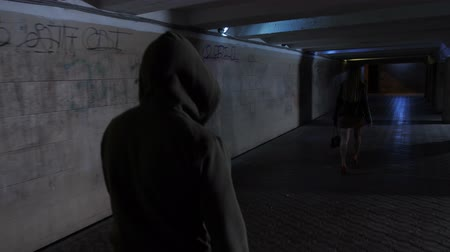 crossway : Man in hoodie chasing woman in dark tunnel