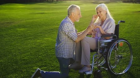 fingers : Senior man on knee proposing woman on wheelchair Stock Footage