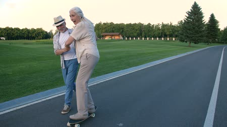 восхищенный : Husband teaching wife to skateboard in summer park