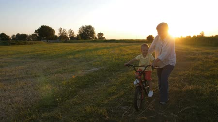 milestone : Grandmother teaching grandson to ride a bike