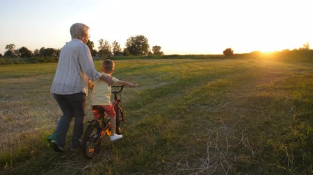 Back view of boy learning to ride bike with granny