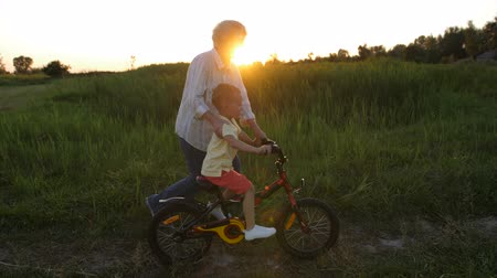 milestone : Toddler boy riding bicycle with grandmothers help Stock Footage