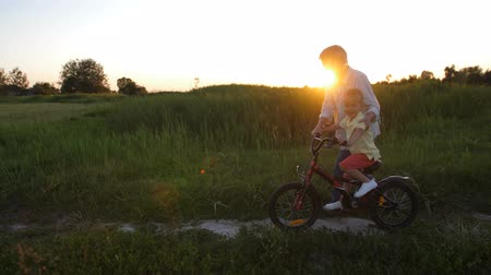 milestone : Elderly granny teaches happy grandson to ride bike Stock Footage