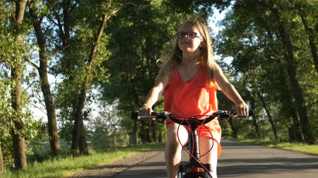 Cute blond teenage girl on bicycle trip in summer Stock Footage
