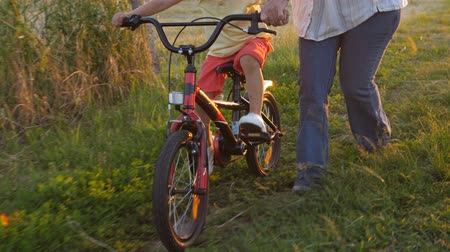 öğrenme : Closeup legs of grandmother and boy on bicycle