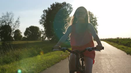 Teenager cycling during sunset in countryside Stock Footage
