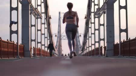 mosty : Slim senior female running across bridge in city Wideo