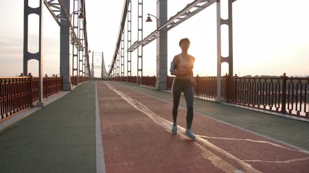 titular : Gorgeous fitness lady running on pedestrian bridge