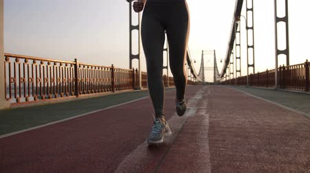 legginsy : Fit muscular female legs running on bridge