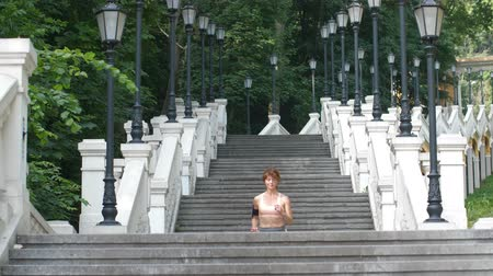 Fit mature female running down the stairs in city Stock Footage