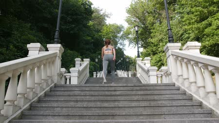Mature woman doing jumping squats on steps in park