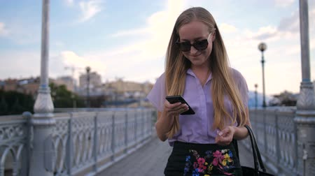 Business lady in sunglasses walking with phone Stock Footage