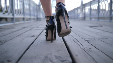 high heel shoe : Closeup sexy feet in high heels walking on bridge