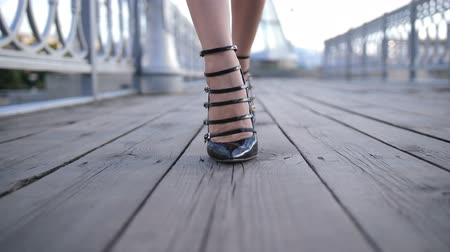 Closeup sexy feet in high heels walking on bridge