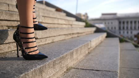 high heels : Legs in high heels stepping down stairs in city