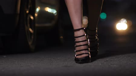 Closeup female legs in high heels walking at night