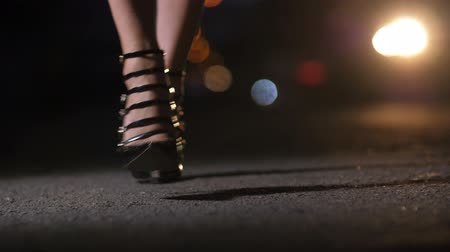 Closeup legs in heels walking with bokeh light