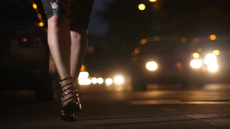 Businesswoman in heels walking on street at night Stock Footage