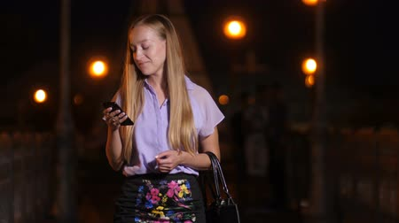 Young woman walking with smartphone and smiling