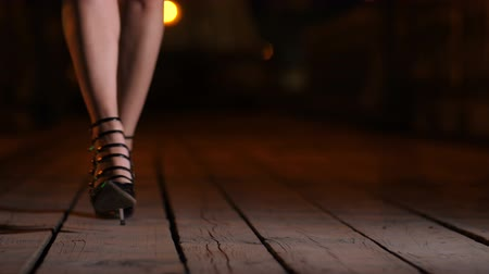 Closeup legs in heels walking on bridge at night