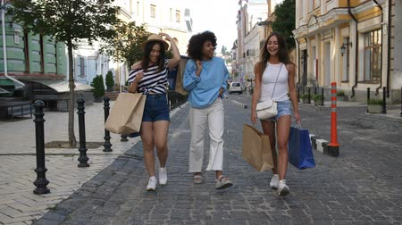 Three multiethnic girls walking with shopping bags