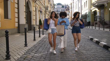Young women walking with phones and shopping bags