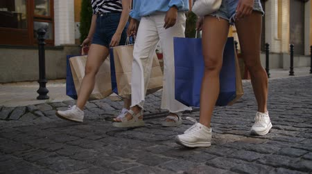Legs of female friends walking with shopping bags Stock Footage