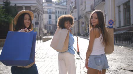 Three multiracial girls with shopping bags smiling Dostupné videozáznamy