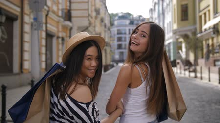 Asian and caucasian shopper friends smiling at cam