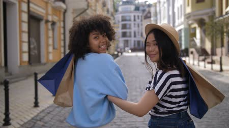 Mixed race and asian shopaholic women smiling Stock Footage
