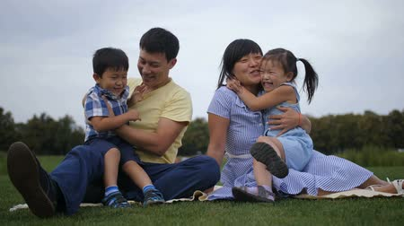 Happy asian parents embracing their joyful kids Dostupné videozáznamy