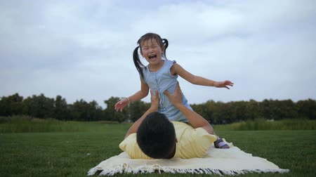 Playful father lifting up cute daughter outdoors