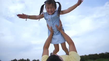 Father playing with his daughter lifting her up