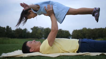 Loving dad raising up his little daughter in park