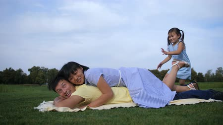 Joyful asian family piled on top of dad in park