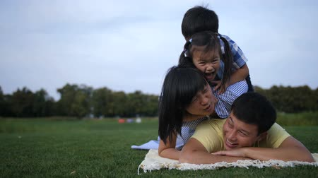 Carefree family making a pile on grass together