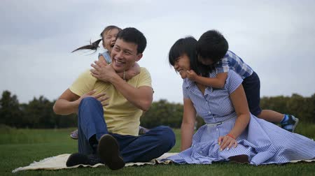 Cute asian siblings embracing parents in nature