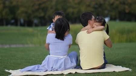 Cute asian kids tenderly embracing parents in park Stock Footage