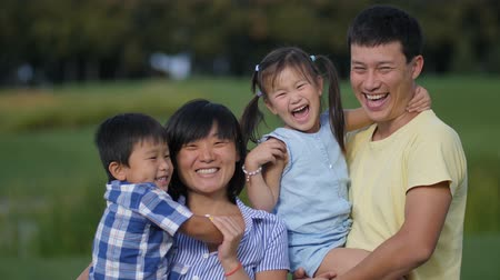 yapıştırma : Excited asian family of four laughing in park Stok Video