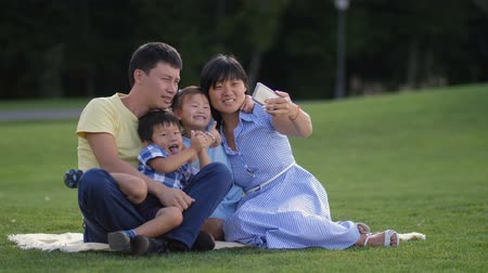 Joyful asian family with kids taking selfie in park