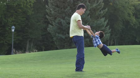 pai : Happy asian father spinning his cute son on meadow