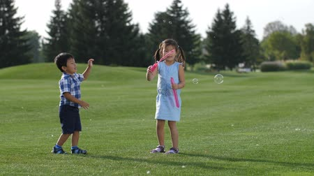 Excited asian siblings having fun with soap bubbles Stock Footage