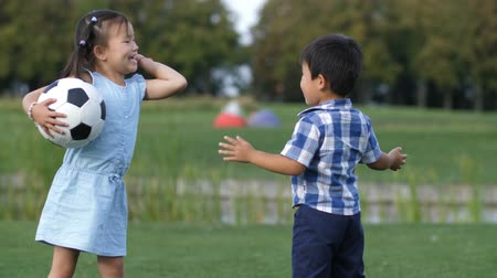 Cheerful asian children with soccer ball in park