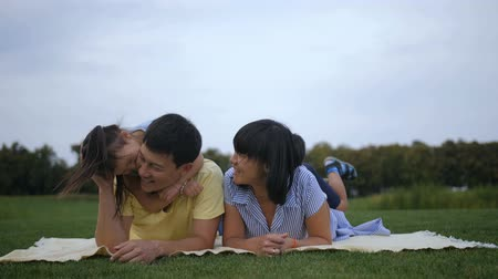 Carefree asian children piled up on top of parents