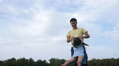 Happy asian father spiining in circle his daughter Stock Footage